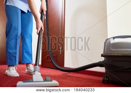Hotel maid cleaning carpet with vacuum cleaner