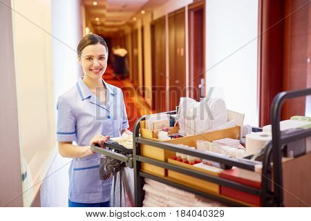 Young female with tidy supplies standing in hotel corridor