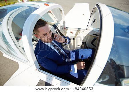 Fast business travel concept: high angle of businessman speaking by phone in jet plane