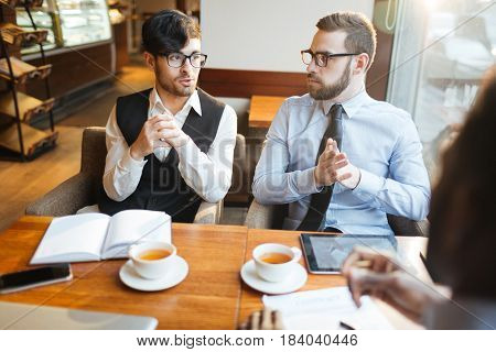 Businessmen sitting in cafeteria and discussing plans