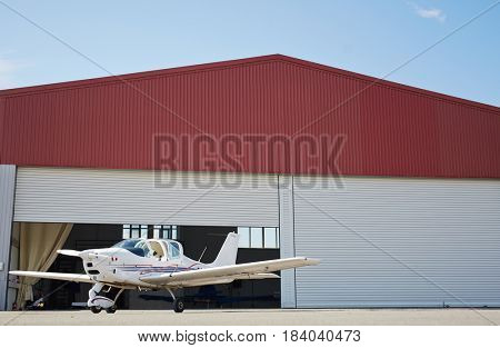 Wide angle graphic image of small jet plane standing in hangar of airport field