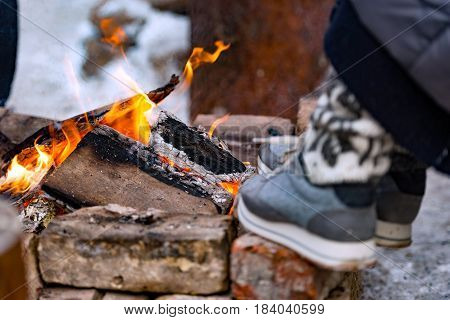 In the cold winter day a person heats feet to the fire.
