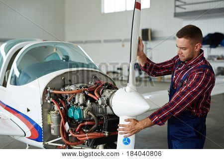 Portrait of modern aircraft engineer repairing jet plane in hangar, disassembling engine and fixing propeller motors
