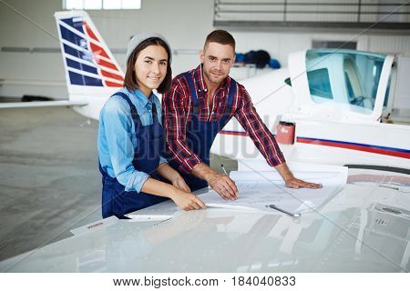 Two modern aircraft engineers, man and woman, looking at camera while working with plane blueprints in airport hangar