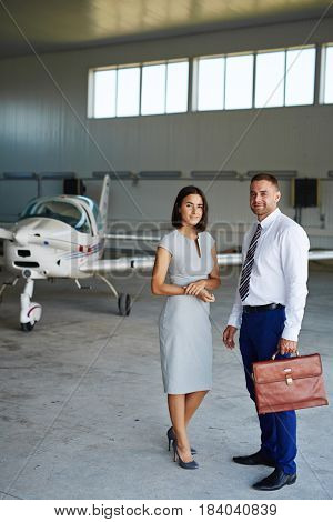Portrait of smiling business people looking at camera while waiting in airport hangar, posing by jet plane