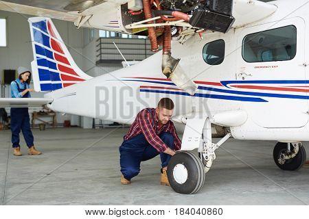 Airplane service crew repairing plane in hangar:  two modern mechanics, man and woman, fixing jet plane