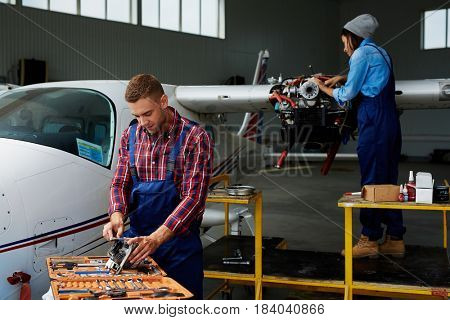 Airplane service crew working on preflight maintenance:  two young mechanics, man and woman, repairing jet plane in hangar