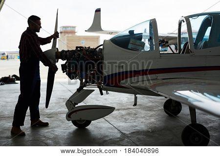 Dark silhouette of aircraft mechanic assembling jet plane in maintenance hangar