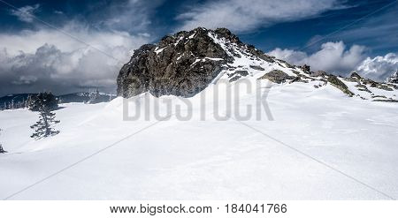 quartzite rock formation on Pecny hill summit in winter Jeseniky mountains in Czech republic with snow and blue sky with clouds