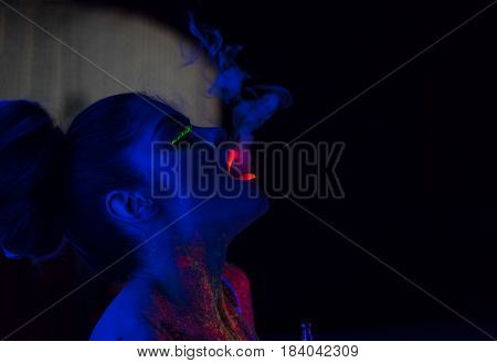 portrait of fashion model woman in uv neon light with fluorescent glowing Body Art make-up. She blows smoke from the hookah. Low key dark image. Soft focus image.
