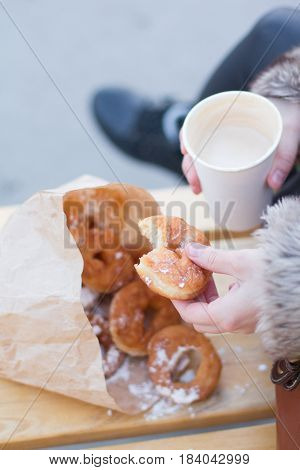 Fast Food. Sugar Donuts In The Hands Of The Girl. Food On The Street - Donuts And Coffee