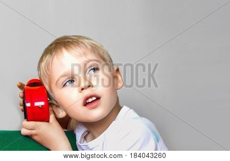 Boy Holding An Alarm Clock, A Child And Time Red, Concept Of Time, Focus On The Alarm Clock, Soft Fo