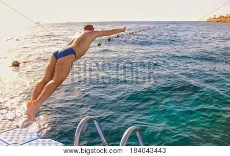 A Man Jumping From The Pontoon Bridge Into The Water, Sport Leisurev