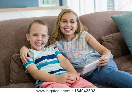 Portrait of smiling sister and brother sitting on couch using mobile phone in living room at home