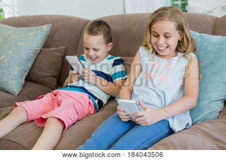Smiling sister and brother sitting on couch using mobile phone in living room at home