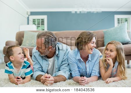 Smiling family lying together on carpet in living room at home