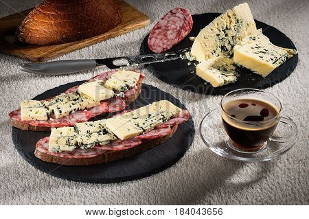 Sandwiches with cheese of Dorblu and raw smoked sausage on black round slate plates, a cheese knife and a cup of hot coffee