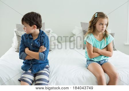 Sad siblings sitting with arms crossed in bedroom at home