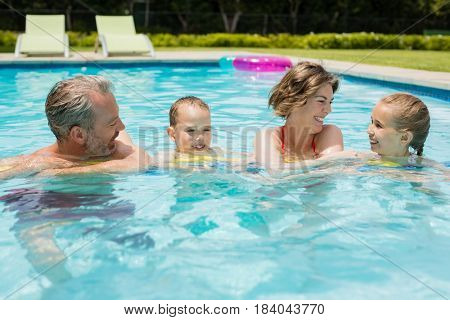 Happy parents and their kids having fun in pool on a sunny day