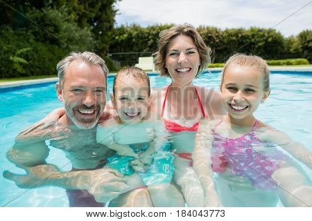 Portrait of happy parents and kids in pool on a sunny day