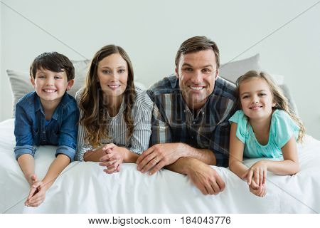 Portrait of smiling family lying on bed in bedroom at home