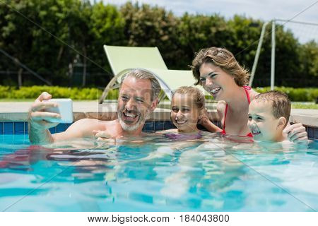 Man taking selfie with family in swimming pool