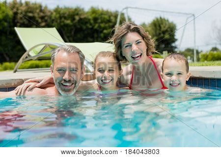 Portrait of smiling family enjoying in swimming pool