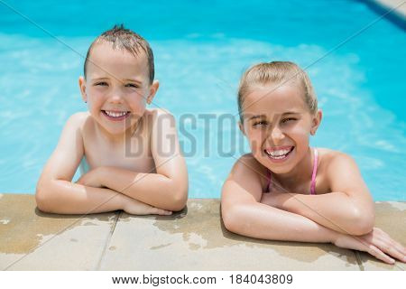Portrait of smiling boy and girl relaxing on the side of swimming pool