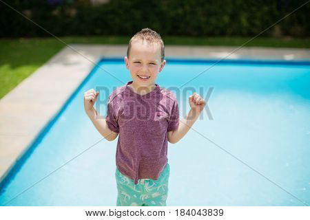 Portrait of smiling girl standing near swimming pool