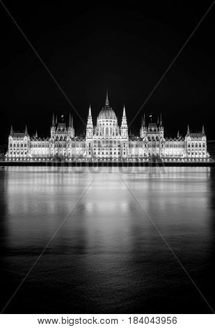 Main landmark of The Hungarian capital - Budapest parliament building reflected in Danube river, black and white photo