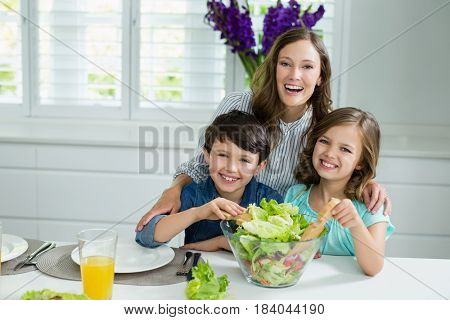 Portrait of smiling mother and childrens mixing bowl of salad in kitchen at home