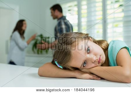 Portrait of sad girl resting on table in living room at home
