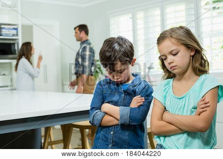 Sad siblings standing with arms crossed while parents arguing in background at home