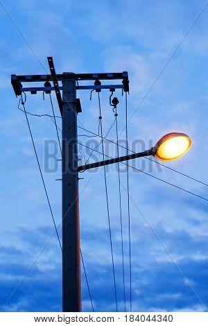 Street light on concrete electricity pole in evening