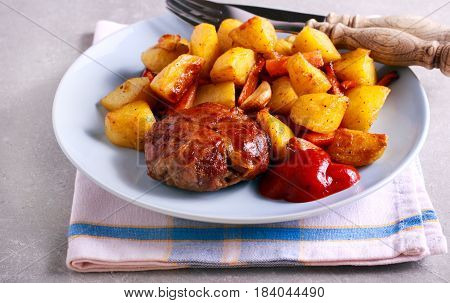 Roasted beefsteak wrapped in bacon strips and potatoes with carrot