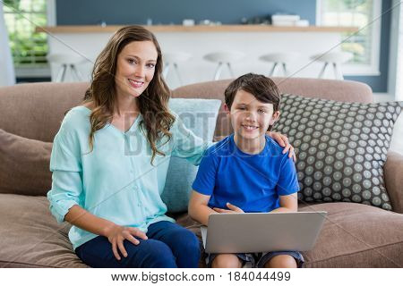 Portrait of smiling mother and son sitting on sofa using laptop in living room at home