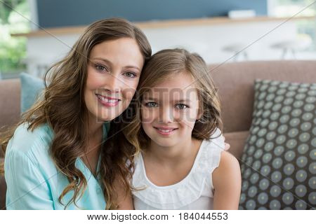 Portrait of smiling mother and daughter sitting on sofa in living room at home