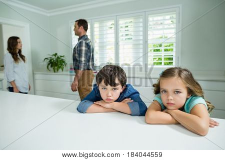 Portrait of sad siblings listening their parents having an argument at home