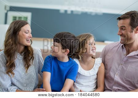 Smiling family sitting on sofa in living room at home