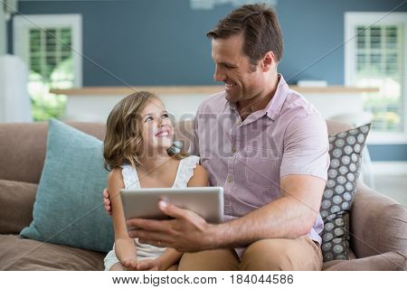 Smiling father and daughter sitting on sofa using digital tablet in living room at home