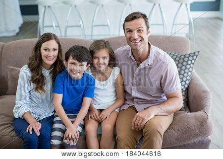 Portrait of smiling family sitting on sofa in living room at home
