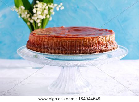 Caramel cheesecake on stand plate over blue background