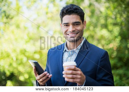 Portrait of businessman holding disposable coffee cup and mobile phone in a park