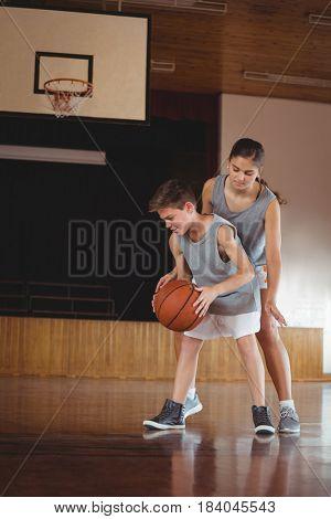 School kids playing basketball in school