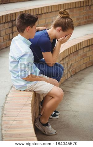 Schoolboy consoling her sad friend on steps in campus at school