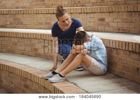Schoolgirl consoling her sad friend on steps in campus at school