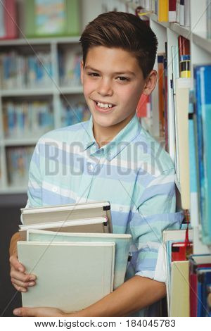Portrait of schoolboy holding books in library at school