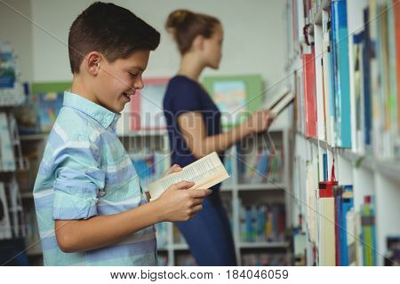 Smiling schoolboy reading book in library at school