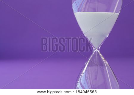 Close-up of hourglass against purple background