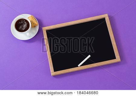 Slate and chalk with black coffee on purple background